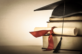 A mortarboard and graduation scroll tied with red ribbon on a stack of old battered book with empty space to the left. Slightly undersaturated with vignette for vintage effect.